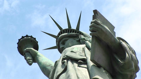 The camera zooms in from beneath the tablet of the Statue of Liberty to her powerful gaze Footage