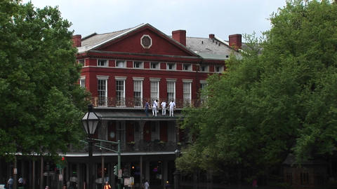 A medium-shot of repairmen, standing on the balcony of an old brick building, doing repairs Footage
