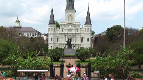 Horse drawn carts and traffic pass by Jackson Square in the New Orleans French Quarter Footage
