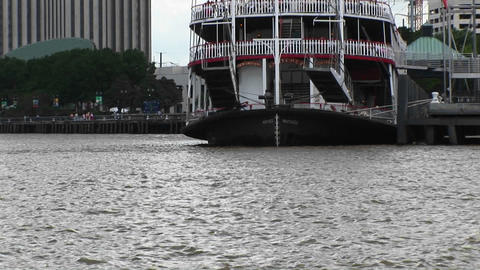 The Mississippi River flows around a paddleboat full of tourists as it sits docked in New Orleans Footage