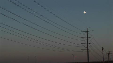 Long-shot the full moon hanging above power lines Stock Video Footage