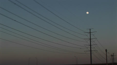 Long-shot the full moon hanging above power lines Footage
