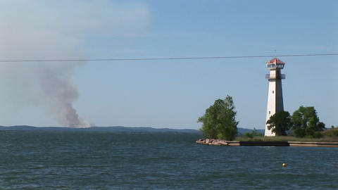 Medium-shot of a lighthouse with smoke rising on the horizon Stock Video Footage