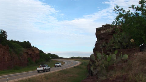 Medium-shot of cars driving on a highway next to a rocky outcropping in Texas Footage