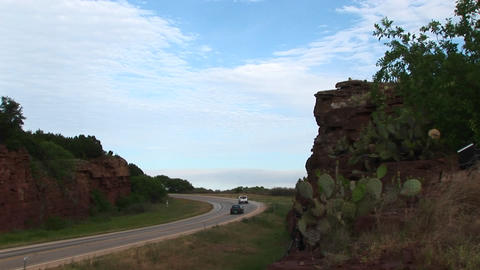Medium-shot of cars driving on a highway next to a rocky... Stock Video Footage