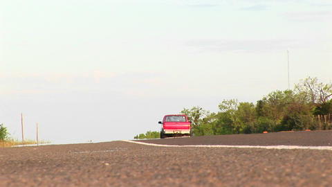 Medium-shot of a pickup driving by on a two-lane Texas road Stock Video Footage