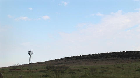 Long-shot of a windmill standing in a pasture in Texas Footage