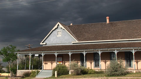 Medium-shot of a ranch house with storm clouds building behind Footage