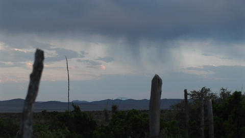 Long-shot of rain clouds moving over a rural landscape Stock Video Footage