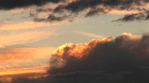Medium-shot of storm clouds rolling into golden clouds Stock Video Footage
