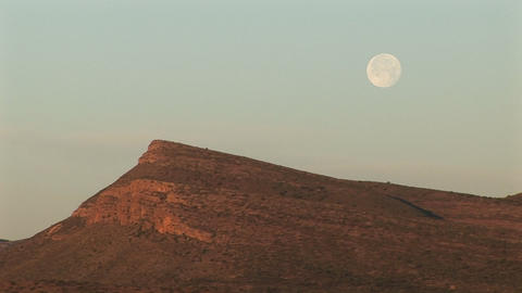 Medium-shot of the moon hovering over a rocky landscape Stock Video Footage