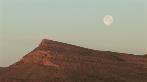 Medium-shot of the moon hovering over a rocky landscape Footage