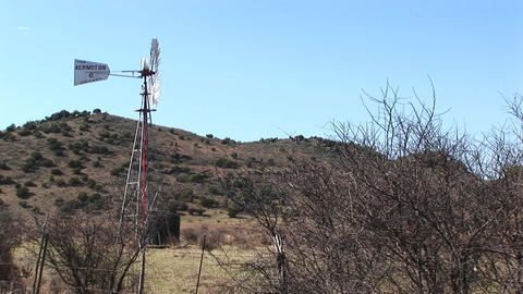 An old windmill turns in the desert Stock Video Footage