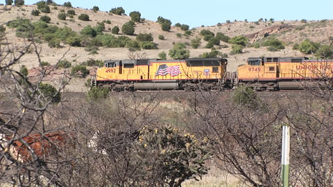 Long-shot of a train passing through desert pasture lands Stock Video Footage
