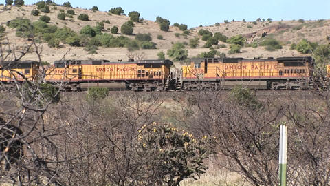 Long-shot of a train passing through desert pasture lands Footage