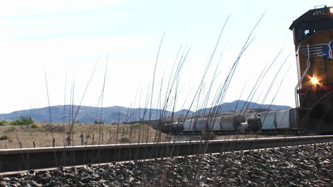 Close up of a train passing on tracks in the desert Stock Video Footage