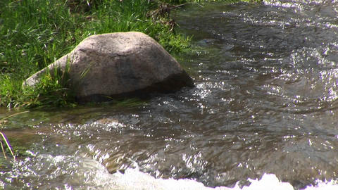 Medium shot of a rock on the bank of a flowing mountain... Stock Video Footage