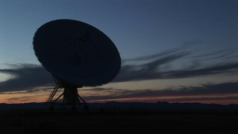Medium-shot of a silhouette of a satellite dish in the array at the National Radio Astronomy Observa Footage