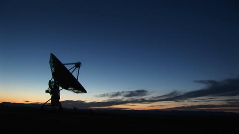 Long-shot of a silhouette of a satellite dish in the array at the National Radio Astronomy Observato Footage