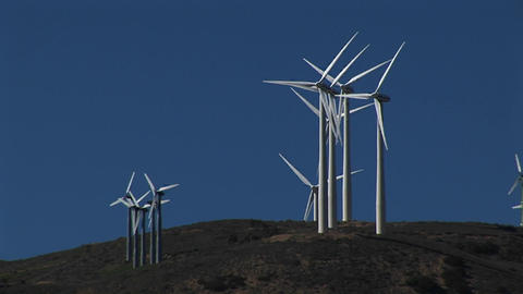 Long-shot of several wind turbines generating power in Tehachapi, California Footage