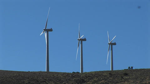 Long-shot of three wind turbines generating power at... Stock Video Footage
