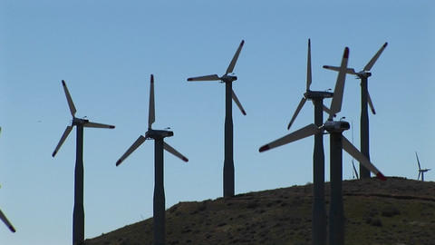 Medium-shot of several wind turbines generating power at Tehachapi, California Footage