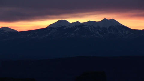 Long-shot of the La Sal Mountains silhouetted against a golden sky Footage