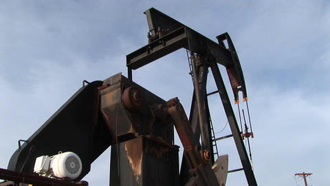Pan-left shot of an oil pump turning in the New Mexico... Stock Video Footage