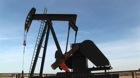 Medium shot of an oil pump turning in the New Mexico desert Footage