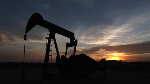 Medium shot of a silhouetted oil pump turning in the New Mexico desert pumping petroleum Footage