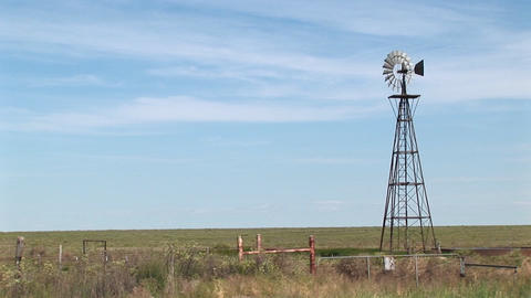 Long shot of a windmill turning in a ranch pasture Footage