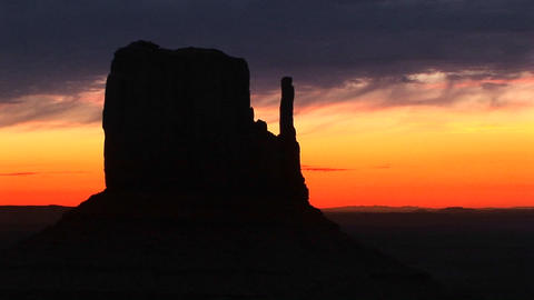 Medium shot of Left Mitten in Monument Valley Arizona silhouetted at golden-hour Footage