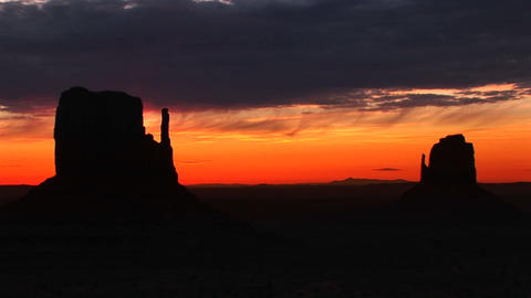 Long-shot of silhouetted Mittens in Monument Valley, Arizona at golden-hour Footage