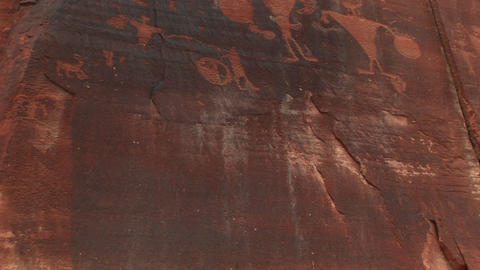 Pan up shot of ancient petroglyphs on a sandstone cliff Footage