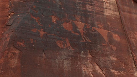 Pan up shot of ancient petroglyphs on a sandstone cliff Stock Video Footage