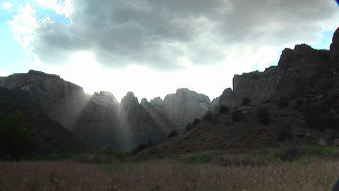 Long shot of rays of sunlight filtering over mountain peaks in Zion National Park Footage