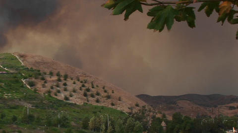 Pan-left shot of smoke billowing from a wild fire raging near a Southern California community Footage
