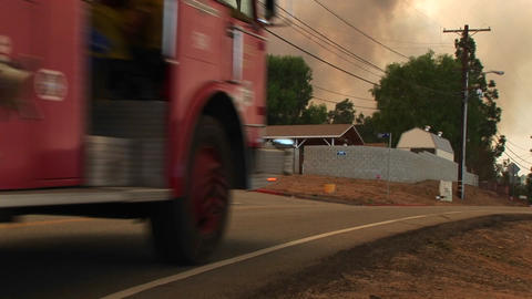 Medium shot of fire trucks racing down a small town... Stock Video Footage