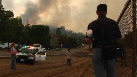 Medium shot of emergency personnel viewing a wildfire from a town in California Footage