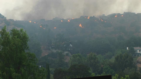 Pan left shot of wildfires burning in the hills near a Southern California community Footage