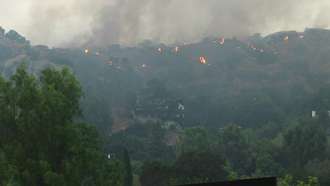 Pan left shot of wildfires burning in the hills near a... Stock Video Footage