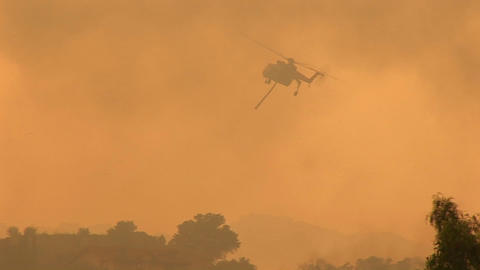 Following shot of a helicopter dropping chemicals on a... Stock Video Footage
