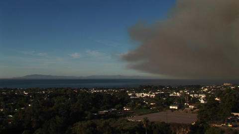 Pan right shot of a California community covered by a cloud of dark smoke from wildfires Footage