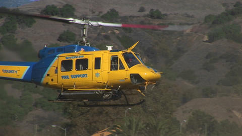 A county fire fighting helicopter lands in a field Stock Video Footage