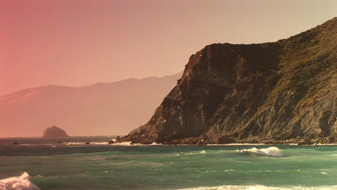 Long-shot of waves splashing up along a steep California... Stock Video Footage