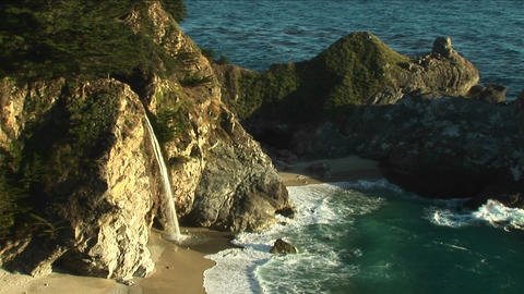 Birds-eye shot of a waterfall crashing down into a secluded pool of the California pacific ocean Footage