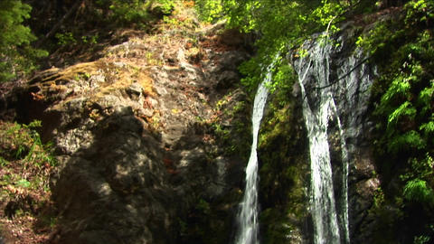 Pan-down of waterfall crashing into a reflecting pool at... Stock Video Footage