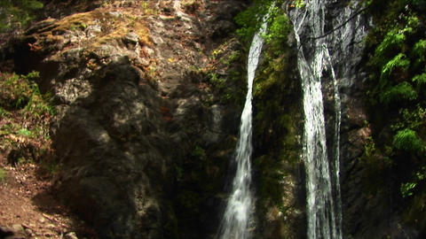 Pan-down of waterfall crashing into a reflecting pool at Big Sur, California Footage