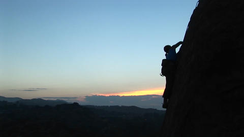 Long-shot of a rock climber scaling a cliff silhouetted... Stock Video Footage
