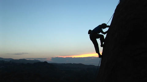 Long-shot of a rock climber scaling a cliff silhouetted against a golden-hour-sky Footage